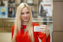 Junge schöne blonde Frau, die selfie mit Handy nimmt Stockfotografie