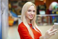 Junge schöne blonde Frau, die selfie mit Handy nimmt Lizenzfreie Stockbilder