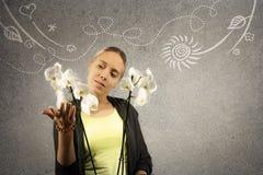 Junge schöne blonde Frau hält weiße Orchidee in den Händen Gekritzelskizze wird auf grauen Beschaffenheitshintergrund gezeichnet Stockbild