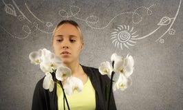 Junge schöne blonde Frau hält weiße Orchidee in den Händen Gekritzelskizze wird auf grauen Beschaffenheitshintergrund gezeichnet Stockfotos