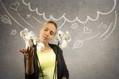 Junge schöne blonde Frau hält weiße Orchidee in den Händen Gekritzelskizze wird auf grauen Beschaffenheitshintergrund gezeichnet Lizenzfreie Stockfotos