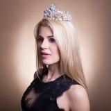 Junge schöne blonde Frau im schwarzen Kleid und in der Krone über Beige Stockfotos
