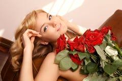 Junge schöne blonde Frau mit Blumen Lizenzfreie Stockfotos