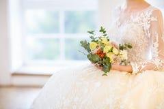 Junge schöne blonde Frau mit dem Blumenstrauß, der in einem Hochzeit dre aufwirft Stockfoto
