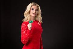 Junge schöne blonde Frau mit Pokerchips über Schwarzem schürhaken Lizenzfreies Stockfoto