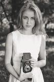 Junge schöne blonde Frau mit Retro- Kamera Stockbild