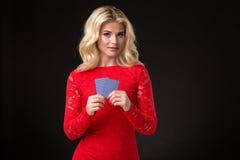 Junge schöne blonde Frau mit Spielkarten über Schwarzem schürhaken Lizenzfreies Stockbild