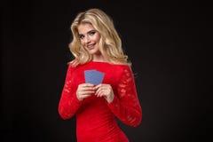 Junge schöne blonde Frau mit Spielkarten über Schwarzem schürhaken Lizenzfreie Stockbilder