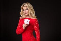 Junge schöne blonde Frau mit Spielkarten über Schwarzem schürhaken Lizenzfreies Stockfoto