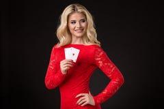 Junge schöne blonde Frau mit Spielkarten über Schwarzem schürhaken Lizenzfreie Stockfotografie