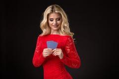 Junge schöne blonde Frau mit Spielkarten über Schwarzem schürhaken Stockfoto