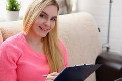 Junge schöne blonde Frau sitzen auf dem Sofa in der Wohnzimmergriffmappe in den Armen Lizenzfreies Stockbild