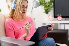 Junge schöne blonde Frau sitzen auf dem Sofa in der Wohnzimmergriffmappe in den Armen arbeiten mit Laptop hören Musik Lizenzfreies Stockfoto