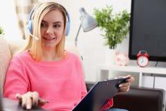 Junge schöne blonde Frau sitzen auf dem Sofa in der Wohnzimmergriffmappe in den Armen arbeiten mit Laptop hören Musik Stockbilder