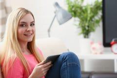Junge schöne blonde Frau sitzen auf dem Sofa in der Wohnzimmergrifftablette in den Armen Stockfotografie
