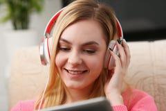 Junge schöne blonde Frau sitzen auf dem Sofa in der Wohnzimmergrifftablette in den Armen hören Musik Stockfoto