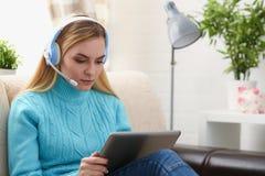 Junge schöne blonde Frau sitzen auf dem Sofa in der Wohnzimmergrifftablette in den Armen hören sonnige Musik Stockfotos