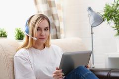 Junge schöne blonde Frau sitzen auf dem Sofa in der Wohnzimmergrifftablette in den Armen hören sonnige Musik Lizenzfreie Stockbilder
