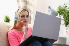 Junge schöne blonde Frau sitzen auf dem Sofa im Wohnzimmergrifflaptop in den Armen hören Musik Lizenzfreie Stockfotos