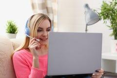 Junge schöne blonde Frau sitzen auf dem Sofa im Wohnzimmergrifflaptop in den Armen hören Musik Lizenzfreies Stockfoto
