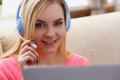 Junge schöne blonde Frau sitzen auf dem Sofa im Wohnzimmergrifflaptop in den Armen hören Musik Stockbilder