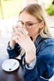 Junge schöne blonde Frau trinkt Kaffee beim Sitzen am Café Lizenzfreie Stockfotografie
