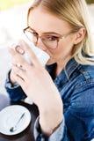 Junge schöne blonde Frau trinkt Kaffee beim Sitzen am Café Lizenzfreies Stockfoto
