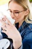 Junge schöne blonde Frau trinkt Kaffee beim Sitzen am Café Lizenzfreie Stockfotos