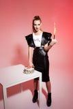 Junge schöne blonde Mädchenstoßhand im Kuchen über rosa Hintergrund Stockfotos