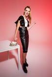 Junge schöne blonde Mädchenstoßhand im Kuchen über rosa Hintergrund Lizenzfreie Stockbilder
