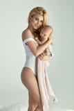 Junge, schöne blonde Mutter mit einem neugeborenen Baby Lizenzfreie Stockfotografie
