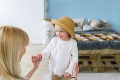 Junge schöne blonde Mutter- und Babytochter im Strohhut, der einander und das Lächeln betrachtet Lizenzfreie Stockfotos