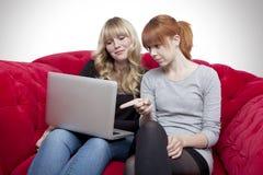 Junge schöne blonde und rote behaarte Mädchen auf rotem Sofa in der Front Stockfotografie