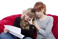 Junge schöne blonde und rote behaarte Mädchen auf rotem Sofa sind trauriges b Lizenzfreies Stockfoto