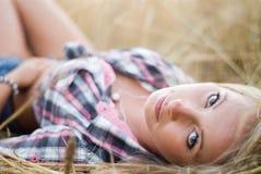Junge schöne Blondine auf einem Gebiet des Kornes Stockfotos