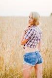 Junge schöne Blondine auf einem Gebiet des Kornes Stockfoto