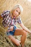 Junge schöne Blondine auf einem Gebiet des Kornes Lizenzfreie Stockbilder
