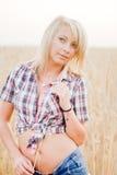 Junge schöne Blondine auf einem Gebiet des Kornes Stockbild