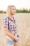 Junge schöne Blondine auf einem Gebiet des Kornes Lizenzfreie Stockfotos