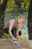 Junge schöne Blondine, die draußen Sportschnürsenkel binden Stockbild