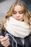 Junge schöne Blondine im Freien in der Straße der hörenden Musik der Stadt Stockfotos