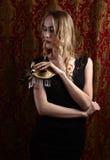 Junge schöne Blondine mit einer Goldvenetianischen Maske Stockfoto