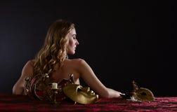 Junge schöne Blondine mit einer Goldvenetianischen Maske Stockbild