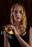 Junge schöne Blondine mit einer Goldvenetianischen Maske Stockfotografie