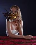 Junge schöne Blondine mit einer Goldvenetianischen Maske Stockbilder