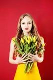 Junge schöne Blondine mit gelber Tulip Flowers Lizenzfreie Stockfotografie