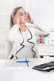 Junge schöne Blondine mit Kopfschmerzen oder Migräne Lizenzfreie Stockbilder