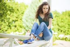 Junge schöne braune behaarte Frau in den Blue Jeans lizenzfreie stockbilder