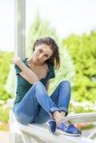Junge schöne braune behaarte Frau in den Blue Jeans lizenzfreies stockfoto