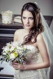 Junge schöne Braut, die Blumenstrauß von Blumen hält. Lizenzfreies Stockfoto